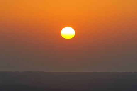 horizont: Red sun next to horizont line in orange sky Stock Photo