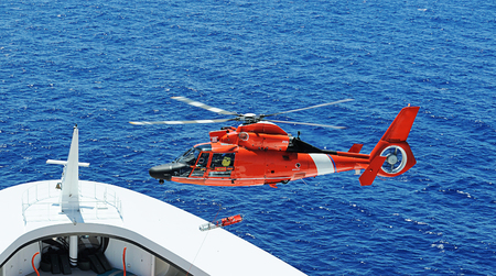ship bow: Rescue helicopter next to ship bow in operation Stock Photo