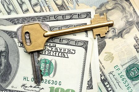 Key on top of dollars laying down Stock Photo