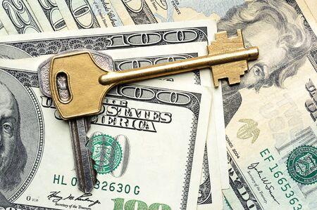 money savings: Key on top of dollars laying down Stock Photo
