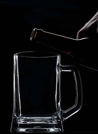 put on: Put beer from bottle on empty glass on black background Stock Photo