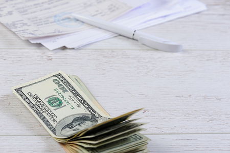 checkbook: count and pay bills with money on wood table