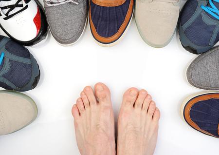 beetwen: bare feet beetwen shoes isolated on white