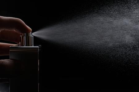 spray perfume on black background close up Standard-Bild