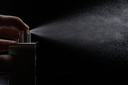 spray perfume on black background close up Stockfoto