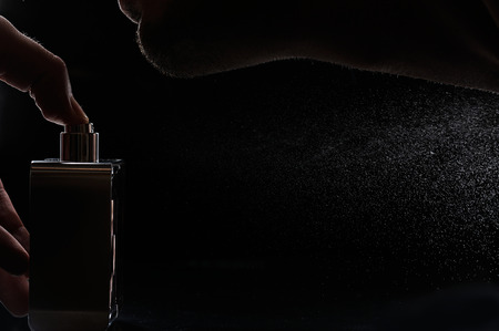 man spray perfume macro on neck black background Stock Photo