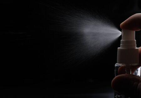 perfume spray: perfume spray from plastic bottle on black background