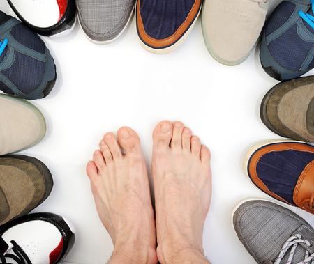 pies masculinos: zapatos zapatillas de deporte COLOURFULL aislados en pie descalzo blanco