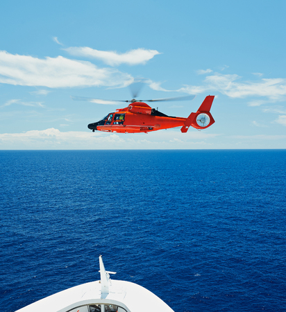 coastguard: Rescue helicopter in sky at sea next to ship Stock Photo