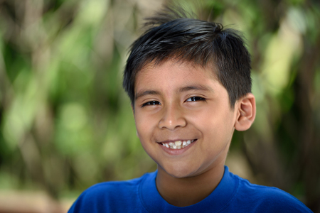 headshot: Headshot of latino boy with smile in nature