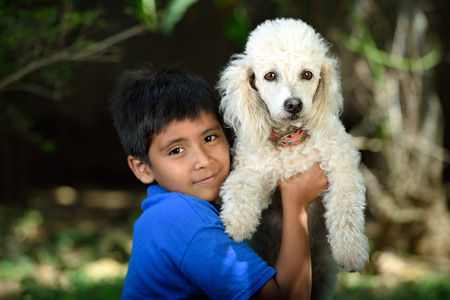 white poodle: white poodle friend of little boy in green park