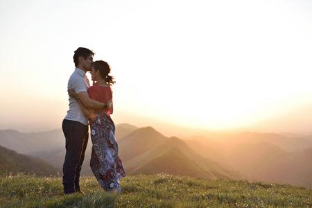 Couple in love meet sunset in green hills landscape