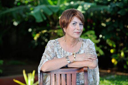 headshot of older smiling woman sitting on park