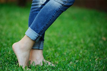 mujer descalza en pantalones vaqueros en el parque de la hierba verde