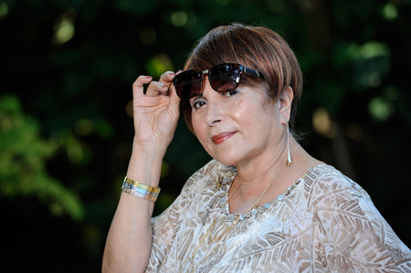 age 60: older rih Woman holding sunglasses on green park Stock Photo