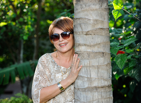 age 60: old rich lady in sunglasses next to tree on garden