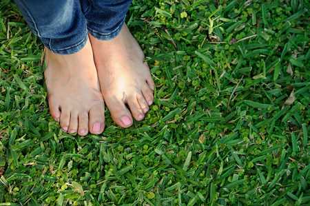 grass beautiful: bare foot on jeans stand on green grass Stock Photo