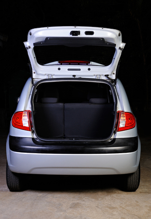 open spaces: open empty  trunk of hatchback isolated on black