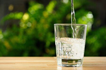 Gießen klares Wasser in transparentem Glas im grünen Garten