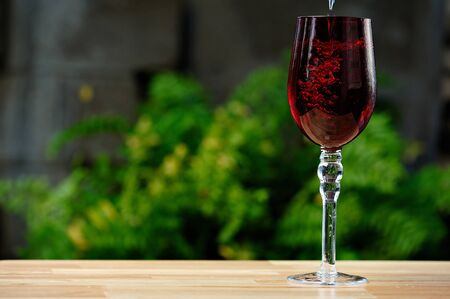 tall glass: pouring drink on red tall glass in green garden Stock Photo