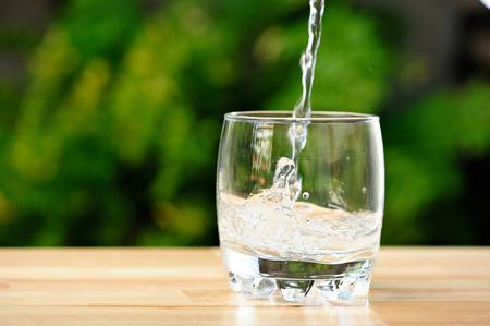 pouring water in empty whisky glass in green garden Standard-Bild