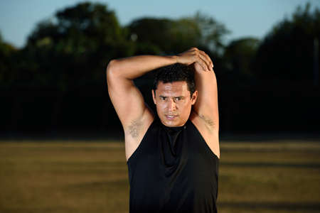 sportman: sportman man stretching body on sunset park