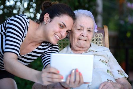 meisje neemt selfie op tablet met oude oma