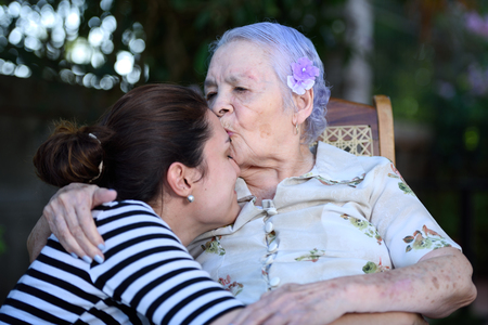 grandaughter: Happy grandma kissing her grandaughter Stock Photo