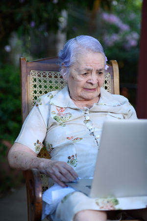 inteligent: Grandma using and talking on a laptop