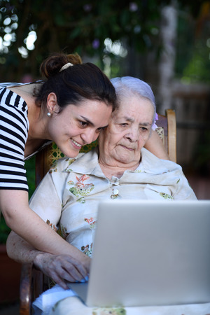 grandaughter: Grandaughter teaching to grandma how to use the laptop