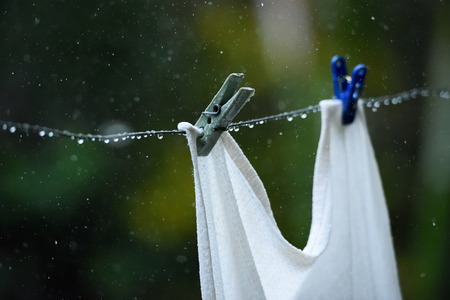 rain wet: wet clothes peg close up during summer rain Stock Photo