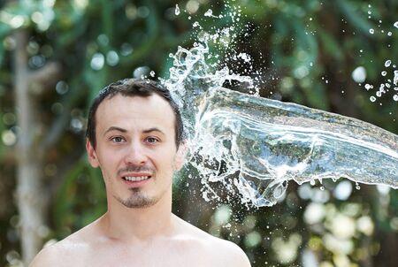 caucasian water drops: water splash punch in man head on green blur background Stock Photo