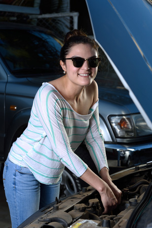 engine bonnet: sexy woman check motor of car outdoor