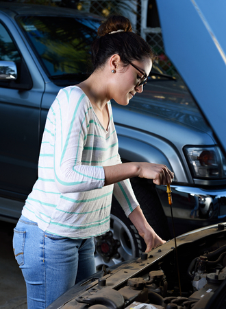 bonnet: young woman check oil in car with open bonnet Stock Photo