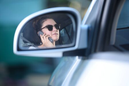 woman mirror: reflection on the mirror of woman talking and driving