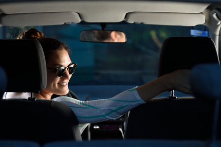 reverse: woman driving a car smiling and going on reverse