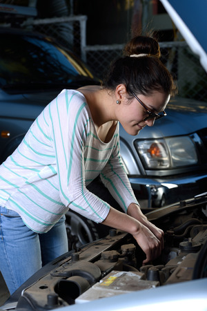 engine bonnet: Girl checking car engine and using sunglasses