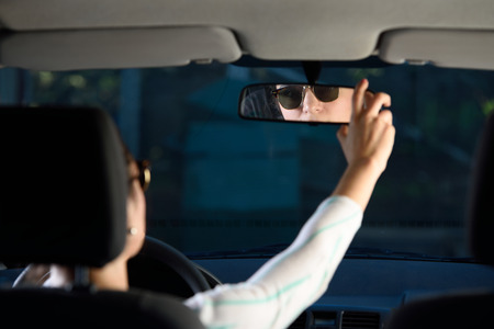 woman adjusting rear mirror while driving a car