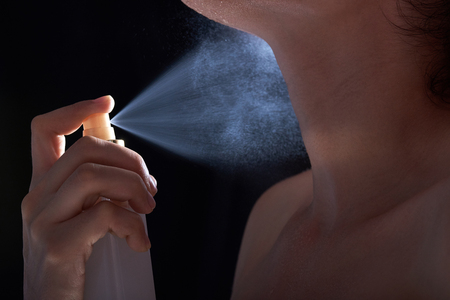 macro young woman spray her skin on black background Stock Photo
