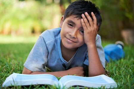 kid tired holding his head while reading a book