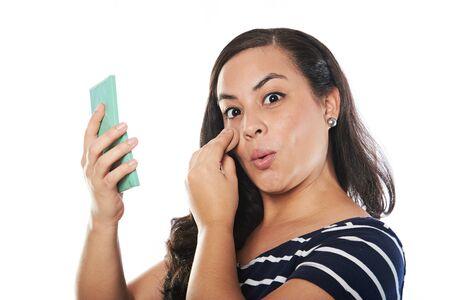 giovane donna mettere cosmetici sul viso isolato su bianco Archivio Fotografico