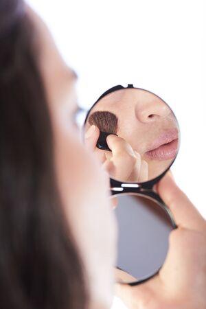 blush: reflection on mirror of girl applying blush Stock Photo