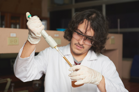 biologist: young biologist take brown sample of dirty water in lab