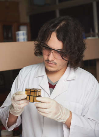 rubik: young man scientist solving a rubik cube in a lab Stock Photo