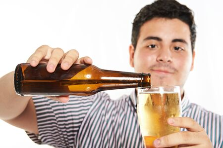 pouring beer: macto of man pouring beer from bottle isolated on white Stock Photo