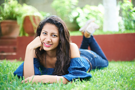 grass beautiful: smiling latino young girl laying on grass