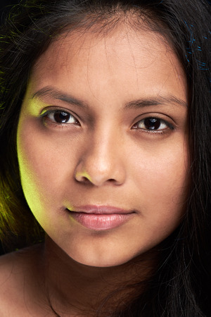 face close up: close up face of young latino woman with green light