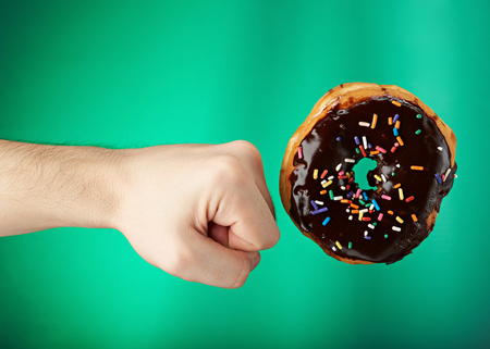 fight hunger: donut got kicked with hand isolated on green background Stock Photo