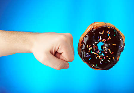 fight hunger: wirst and chocolate donut  isolated on blue background