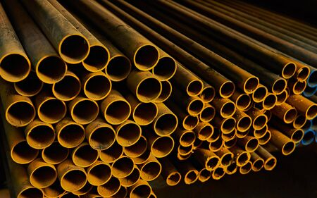 stack of coloured iron round tubes in warehouse